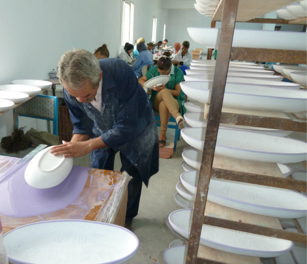 A final glaze is added to the Aqua Fish platter before going into the kiln.